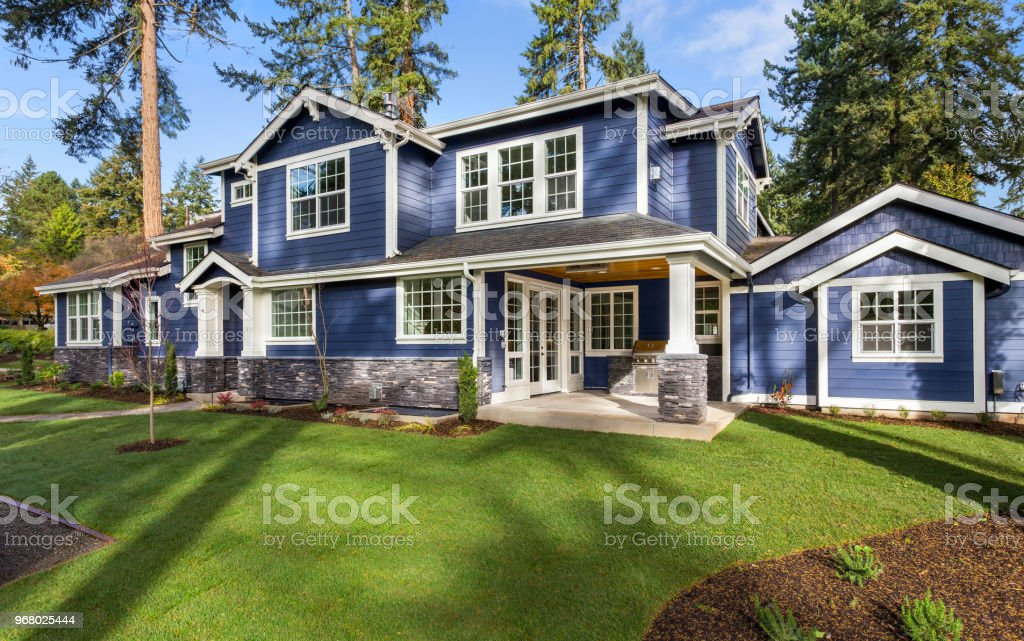 Beautiful luxury home exterior on bright sunny day with green grass and blue sky stock photo
