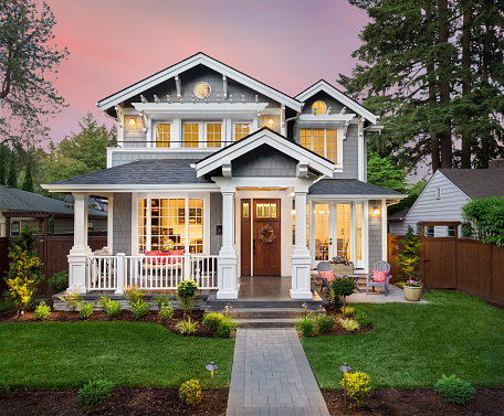 Beautiful luxury home exterior with glowing interior lights at sunset in suburban neighborhood