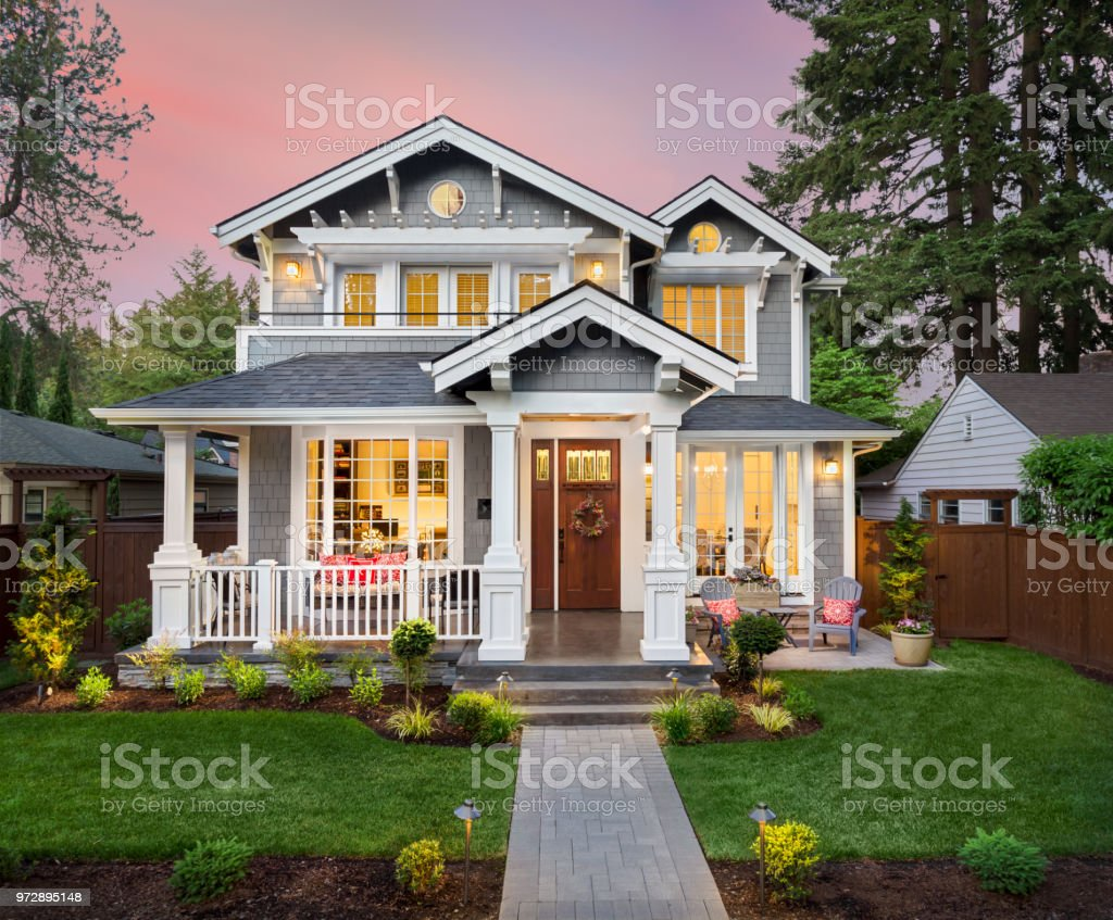 Beautiful luxury home exterior with glowing interior lights at sunset in suburban neighborhood stock photo