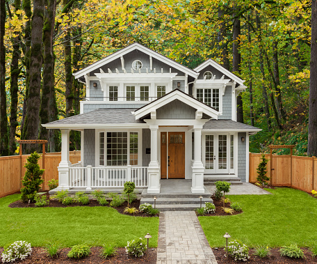 Beautiful Luxury Home Exterior with Green Grass and Landscaped yard. Colorful Forest forms Backdrop of Home.