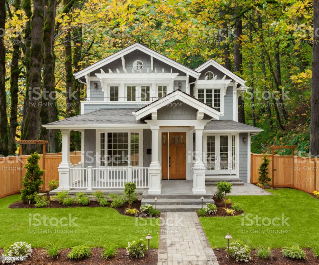 Beautiful Luxury Home Exterior with Green Grass and Landscaped yard. Colorful Forest forms Backdrop of Home. stock photo