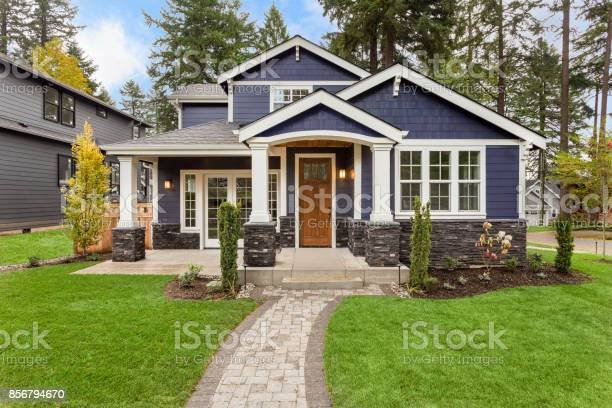 Photo of Beautiful Luxury Home Exterior with Green Grass and Landscaped yard