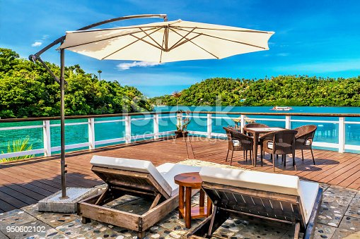 Vibrant blue sky, turquoise water and green trees in the background. The deck is made of natural materials, wood and stone. There are tables and chairs and a sun umbrella provides shade.