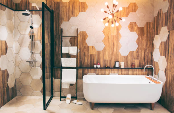 Beautiful luxury vintage empty bathtub  Freestanding white bath. bathroom is beautifully decorated with wooden tiles and electric lamps. stock photo