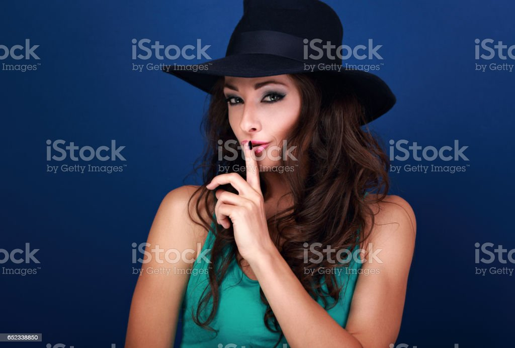 Beautiful makeup female model in hat showing secret sign on blue background with empty copy space. Closeup portrait stock photo