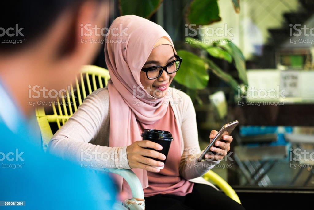 Beautiful malay woman on a coffee break texting zbiór zdjęć royalty-free