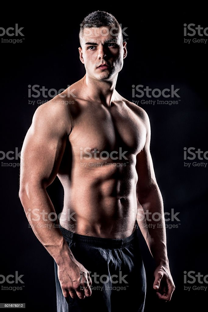 beautiful male athlete shirtless isolated over black background stock photo