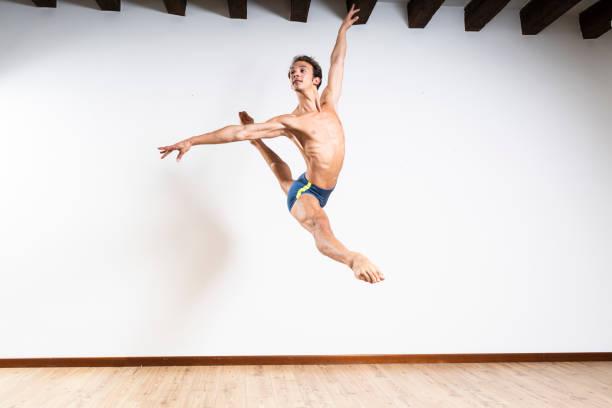 Beautiful male ballet dancer performing indoor stock photo