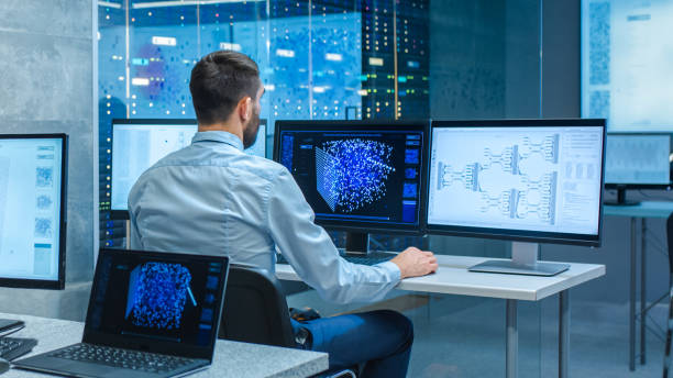 Beautiful Male Computer Engineer and Scientists Create Neural Network at His Workstation. Office is Full of Displays Showing 3D Representations of Neural Networks. Beautiful Male Computer Engineer and Scientists Create Neural Network at His Workstation. Office is Full of Displays Showing 3D Representations of Neural Networks. order stock pictures, royalty-free photos & images