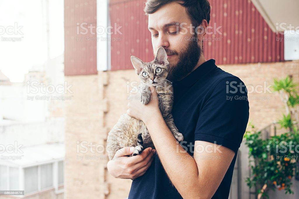 Beautiful man holding and hugging cute curious devon rex cat stock photo