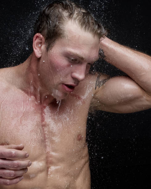 Beautiful man taking a shower - headshot stock photo