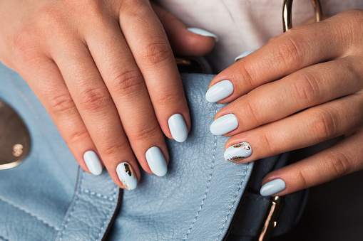 istock Beautiful manicure. Gel polish coating in blue, embossing. 670271534