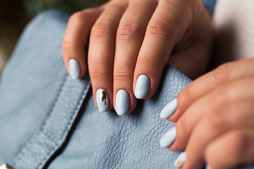 istock Beautiful manicure. Gel polish coating in blue, embossing. 670271564