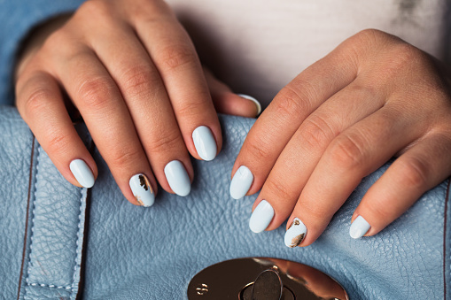 istock Beautiful manicure. Gel polish coating in blue, embossing. 682864920