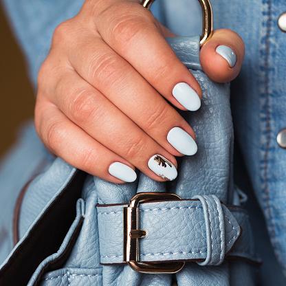 istock Beautiful manicure. Gel polish coating in blue, embossing. 682864928
