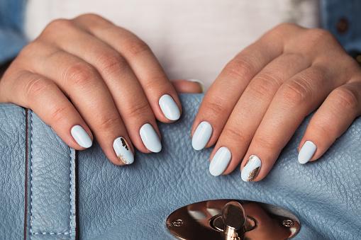 istock Beautiful manicure. Gel polish coating in blue, embossing. 683523094