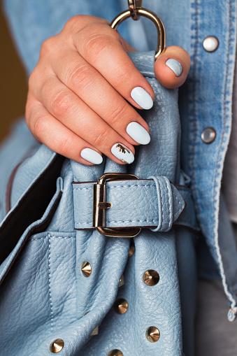 istock Beautiful manicure. Gel polish coating in blue, embossing. 683523112