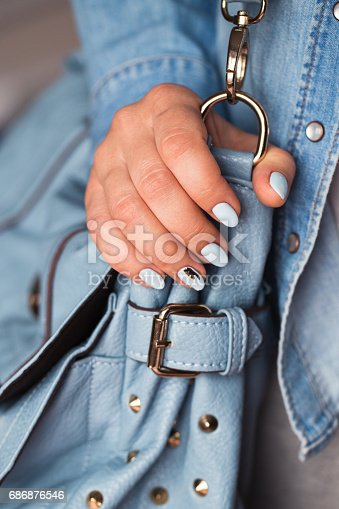 istock Beautiful manicure. Gel polish coating in blue, embossing. 686876546