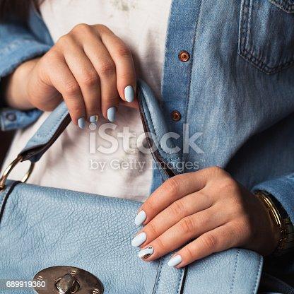 istock Beautiful manicure. Gel polish coating in blue, embossing. 689919360