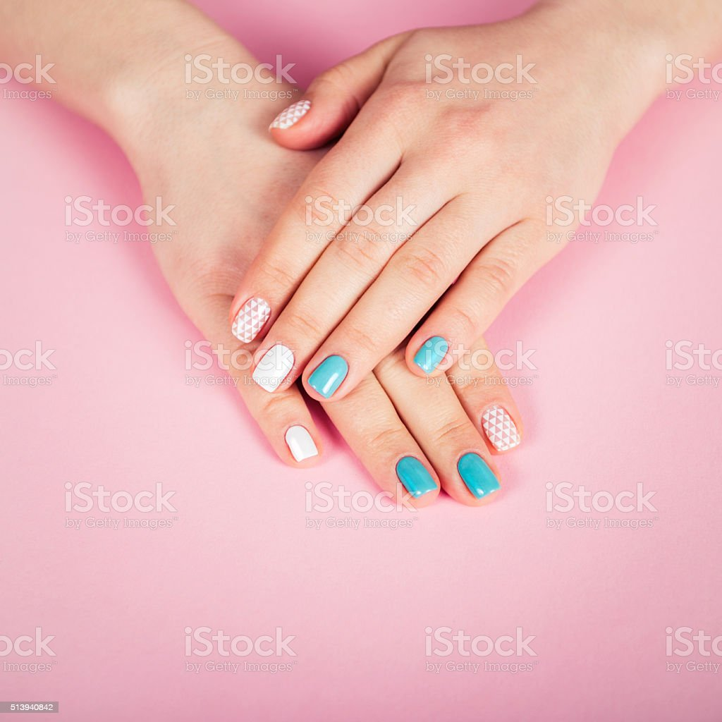 beautiful manicure. gel polish coating in white and turquoise stock photo