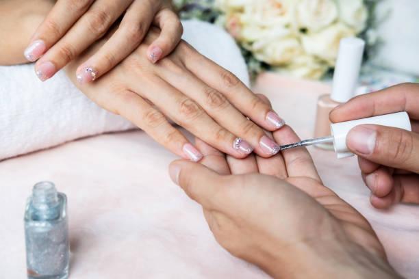 schöne maniküre nägel farben mit glitzer und lack im nagelstudio - nägel glitzer stock-fotos und bilder