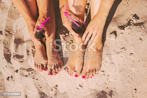 istock Beautiful manicure on women legs on sunny beach 1210160684