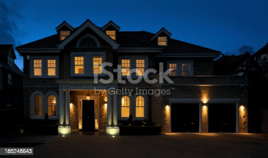 a beautiful and substantial house photographed at dusk with all of the lights switched on. An impressive entrance with black front door is bordered by large double columns and is surrounded with an assortment of windows that are arched on the ground floor.Looking for exterior views of Luxury Homes and Buildings... then please see my other images by clicking on the lightbox Link below...A>A