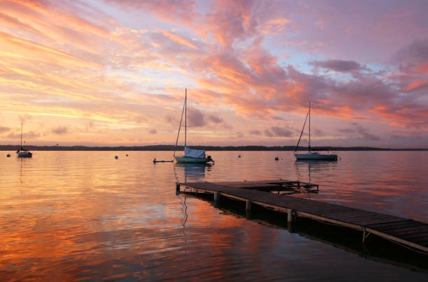 Beautiful marine after sunset background. Amazing summer evening landscape with group of drifting yachts on a lake Mendota during spectacular sunset. Bright sky reflects in the lake water. Madison, WI, Midwest USA. madison wisconsin stock pictures, royalty-free photos & images