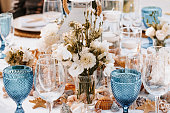 Beautiful maritime Boho Wedding table decoration with blue drinking glasses, selective focus