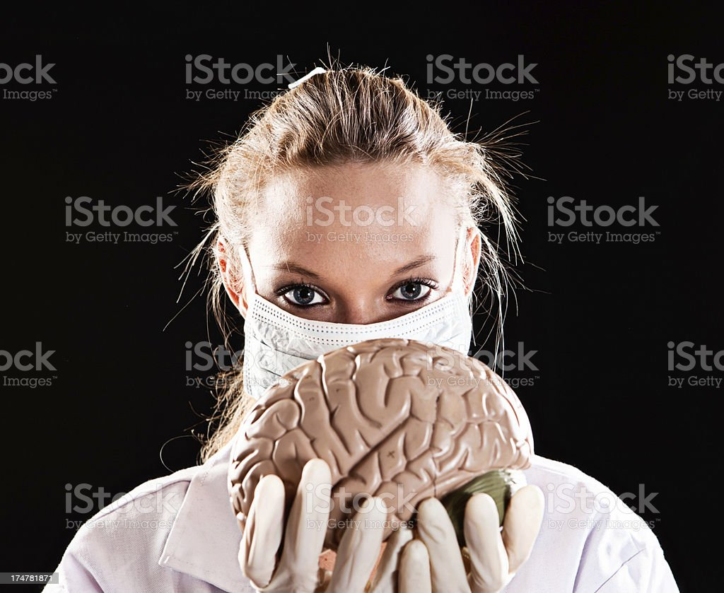 Beautiful masked medical professional holds anatomical model of human brain royalty-free stock photo