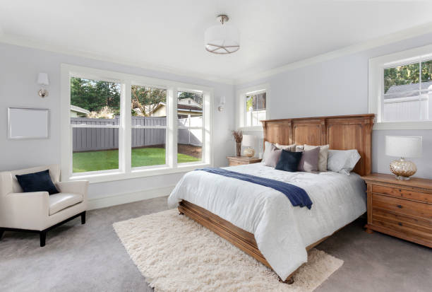 Beautiful master bedroom in new luxury home. Has large bank of windows stock photo