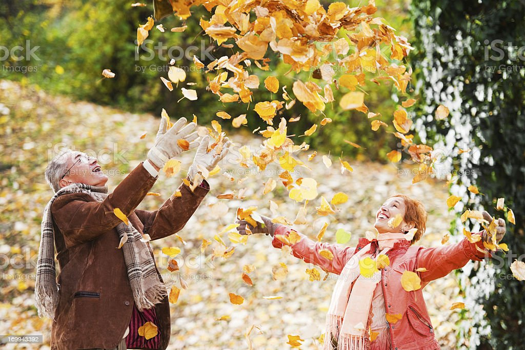 Beautiful mature couple in the heap of leaves. royalty-free stock photo
