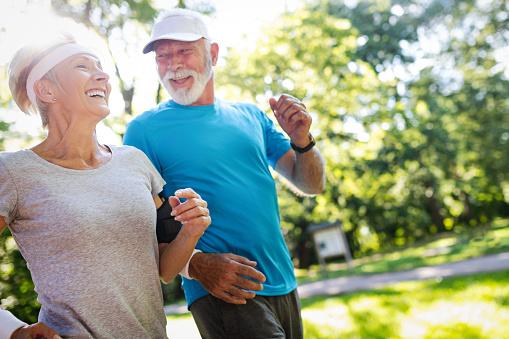 Beautiful senior couple jogging in nature living healthy