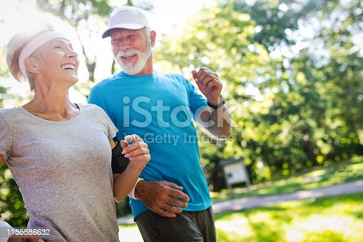 Beautiful senior couple jogging in nature living healthy