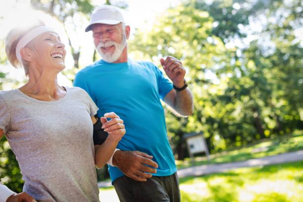 piękna dojrzała para biegająca w naturze zdrowa - dojrzały zdjęcia i obrazy z banku zdjęć