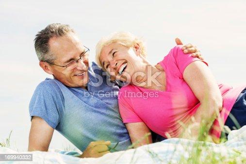 510491454 istock photo Beautiful mature couple lying in nature 169940332