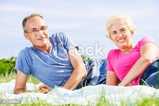 510491454 istock photo Beautiful mature couple lying in nature 471438847
