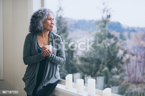 istock Beautiful mature ethnic woman stands by her window in the early morning with a cup of tea and contemplates the day ahead. 867197232