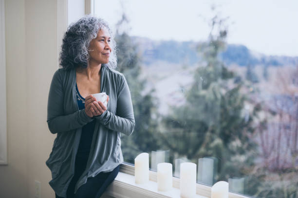 beautiful mature ethnic woman stands by her window in the early morning with a cup of tea and contemplates the day ahead. - hawaiian ethnicity stock photos and pictures