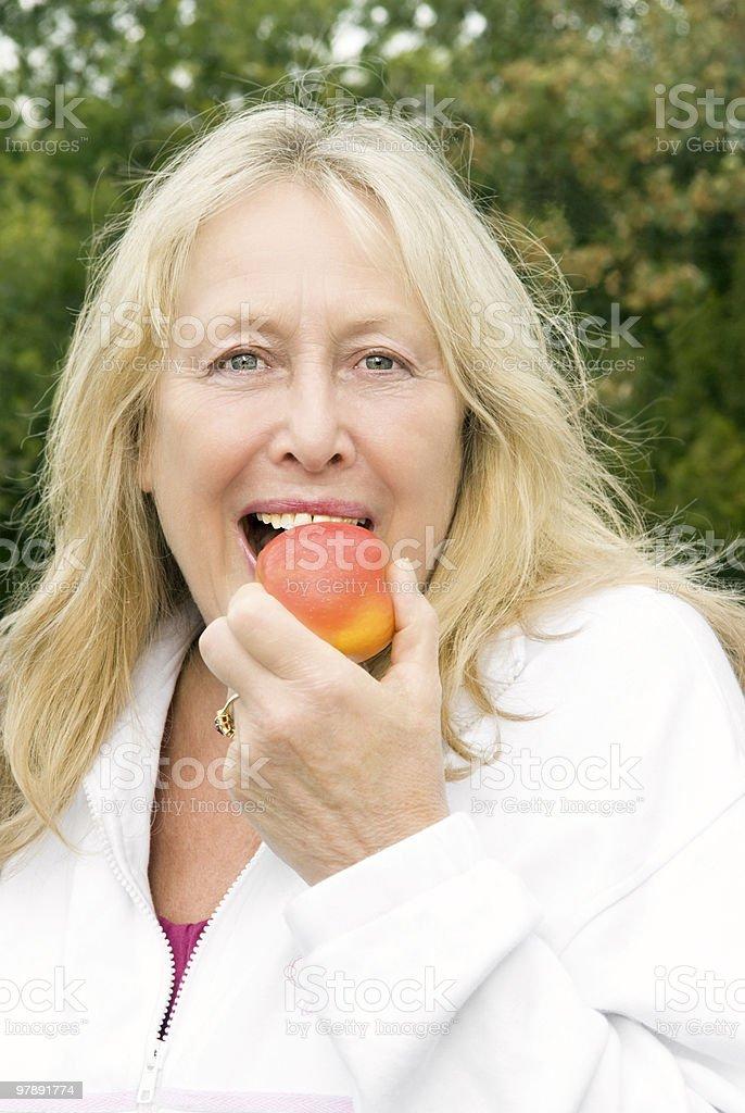 beautiful mature female biting into apple royalty-free stock photo
