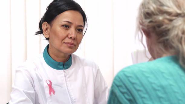 schöne reife ärztin im gespräch mit ihren patienten - symptome brustkrebs stock-fotos und bilder