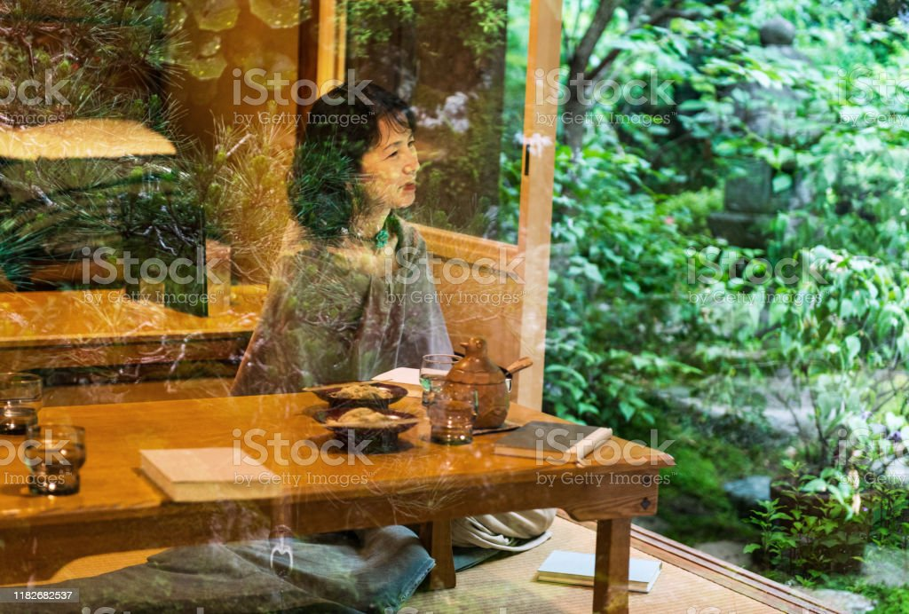 Beautiful Mature Japanese Woman At Restaurant With Green Trees Reflecting On Window Stock Photo Download Image Now Istock