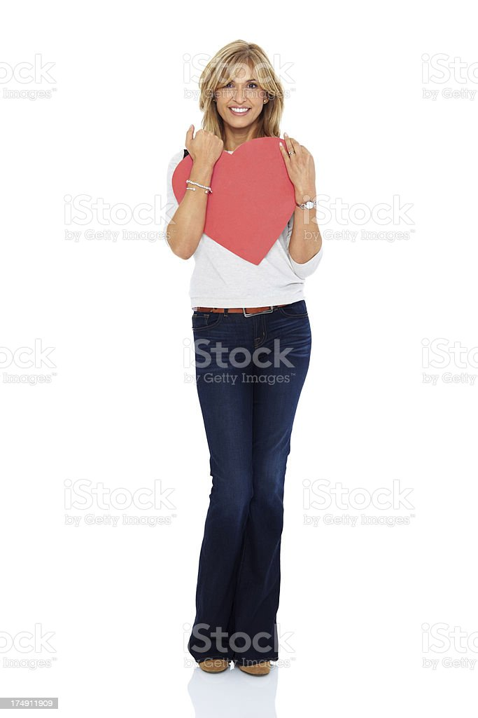 Beautiful mature lady holding a red heart symbol royalty-free stock photo
