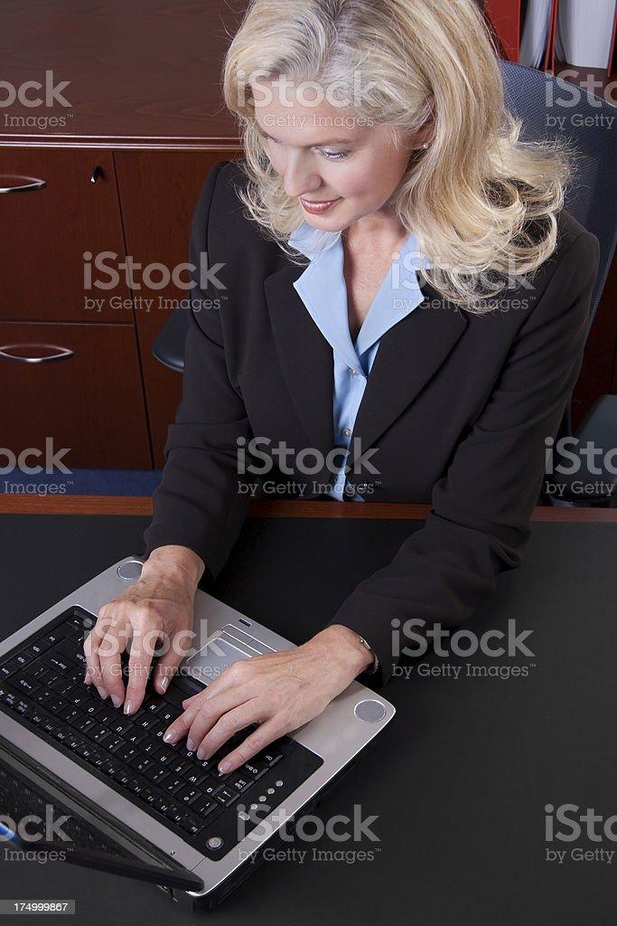 Beautiful mature level business woman on laptop royalty-free stock photo