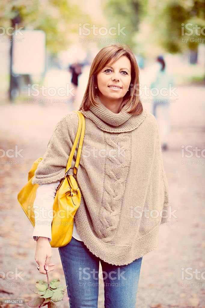 Beautiful mature woman in the park stock photo