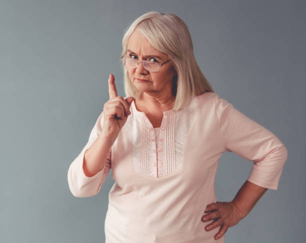 Beautiful mature woman Beautiful mature woman in eyeglasses is warning and looking at camera, on gray background scolding stock pictures, royalty-free photos & images