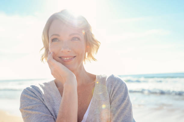 Beautiful mature woman portrait on the beach. stock photo