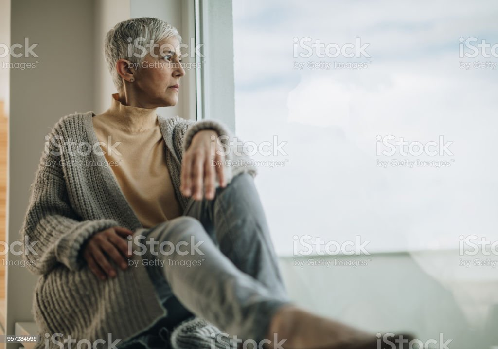Senior woman looking through the window and thinking about something....