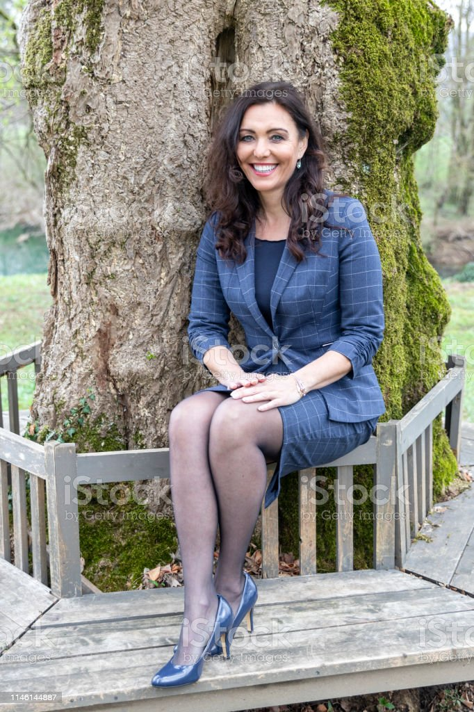 Beautiful Mature Woman Sitting On A Bench In A Park Stock