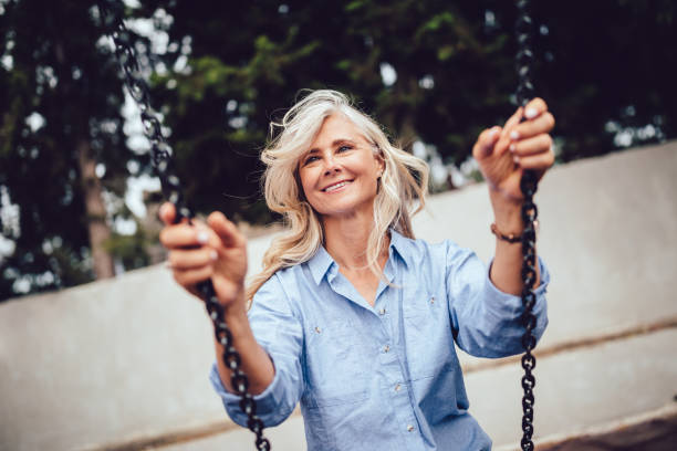 Beautiful mature woman sitting on swing and having fun stock photo